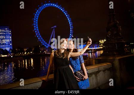 Dos amigas jóvenes tomando el autorretrato en la noche, Londres, Reino Unido. Imagen De Stock