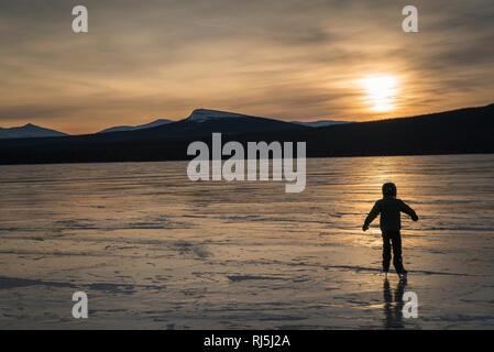 Niño patinando sobre un lago congelado Imagen De Stock