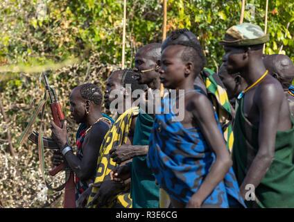 Suri tribu guerreros desfilan ante un donga ritual de combate con palo, valle de Omo Kibish, Etiopía Imagen De Stock
