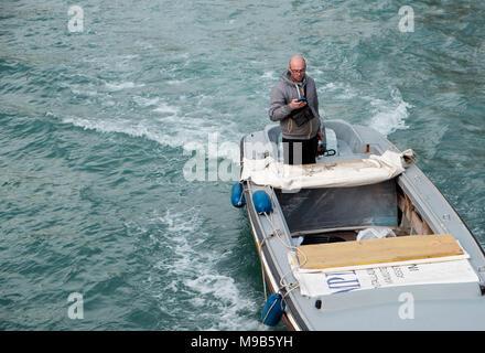 Hombre utilizando el teléfono móvil durante la conducción en bote río Novo canal de Venecia Imagen De Stock