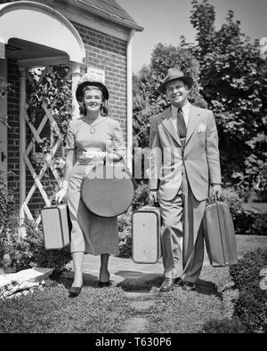 1940 1950 PAREJA HOMBRE MUJER salir de casa mirando a la cámara comienza un viaje llevar equipaje MALETAS Y HATBOX - S985 HAR001 HARS ALEGRÍA LIFESTYLE mujeres casadas casas cónyuge maridos SALUBRIDAD HOME VIDA AMISTAD ESPACIO COPIA DE LONGITUD COMPLETA PERSONAS DAMAS VARONES EDIFICIOS RESIDENCIALES CONFIANZA B&W tiempo de contacto con los ojos fuera de traje y corbata felicidad alegre aventura ESCAPADA DE PLACER DIRECCIÓN CASAS DE VACACIONES sonrisas alegres elegante residencia HATBOX guantes blancos sombreros sombrero cooperación mediados de adulto-adulto medio HOMBRE-MUJER ADULTA MEDIA COMPAÑERISMO VACACIONES ESPOSAS INICIO BLANCO Y NEGRO la etnia caucásica Imagen De Stock