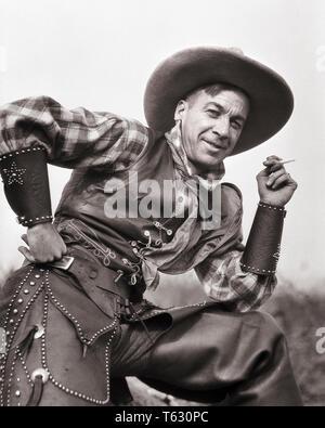 1920 American Cowboy de cuero chaleco sin detonar CHAPS MUÑECA fumar un cigarrillo mirando a la Cámara - t6977 HAR001 HARS LIFESTYLE HISTORIA EMPLEOS CASA RURAL LA VIDA Ejemplar de media longitud espacial personas varones de riesgo profesión occidental la confianza AMERICANA VEST EXPRESIONES B&W contacto ocular cigarrillos vaqueros ocupación habilidades Habilidades felicidad alegre aventura carreras manguitos de ángulo bajo orgullo ocupaciones sonrisas alegres en la cadera mano elegante CAMISETA PLAID CHAPS Mediados de-adulto hombre adulto medio EN BLANCO Y NEGRO la etnia CAUCÁSICA HAR001 ANTICUADO Imagen De Stock