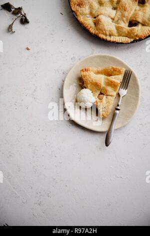 Una rebanada de un pastel de manzana, servido con una bocha de helado de vainilla Imagen De Stock