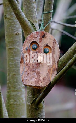 Máscara de madera atados a los árboles en el jardín Imagen De Stock