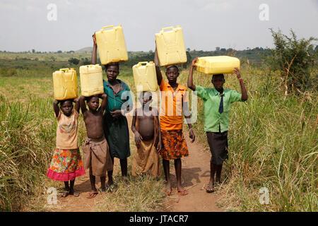 Los niños ugandeses a acarrear agua, Masindi, Uganda, África Imagen De Stock