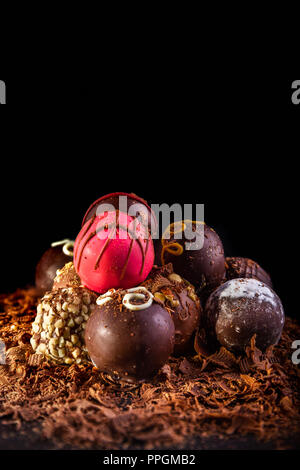 Conjunto de trufas de chocolate surtidas iluminado con una iluminación más creativa, el enfoque selectivo, fondo negro y alojamiento para copiar el espacio. Imagen De Stock