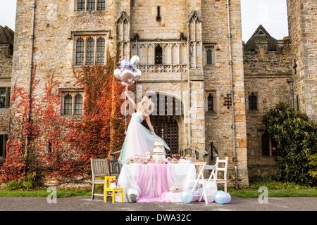 Novia de pie en la tabla fuera de castillo, sosteniendo globos Imagen De Stock