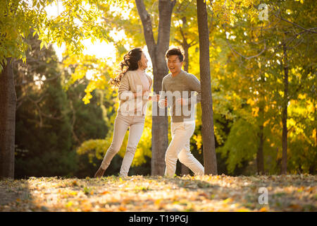Joven pareja feliz corriendo en maderas Imagen De Stock