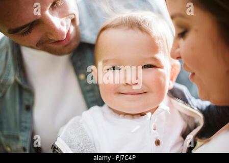 Los padres celebración cute Baby Boy mirando a la cámara Imagen De Stock