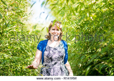Retrato de una sonriente joven mujer de pie contra plantas Imagen De Stock