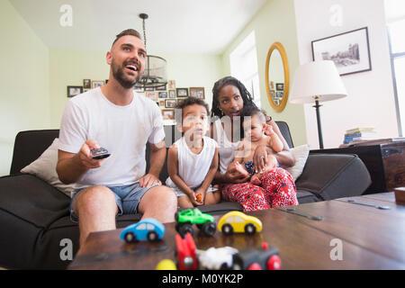 Ver la televisión con padre hijo e hija. Imagen De Stock