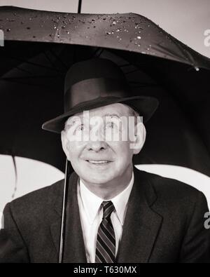 1950 1960 ANCIANO bajo el paraguas MIRANDO HACIA ARRIBA A LAS GOTAS DE LLUVIA - s8706 HAR001 HARS hasta ancianos previsión cae CONCEPTUAL MIRANDO EN BLANCO Y NEGRO la etnia CAUCÁSICA HAR001 METEOROLOGÍA PRECIPITACIÓN ANTIGUA Imagen De Stock