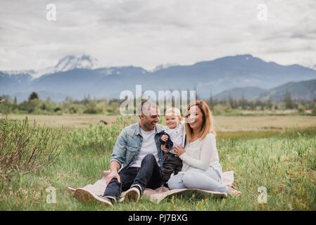 Padres e hijo sentado en el ámbito rural con montañas en segundo plano. Imagen De Stock