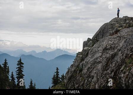 Excursionista macho pararse en la cima robustos, mirando a ver, perro de montaña, BC, Canadá Imagen De Stock