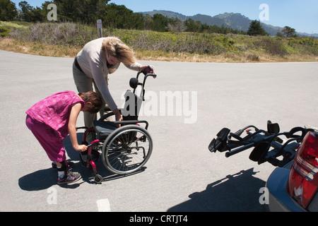 Mamá prepara la silla de ruedas para duaghter viajen en un sendero de trekking. Imagen De Stock