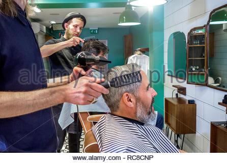 Barber cortando el cabello del cliente. Imagen De Stock
