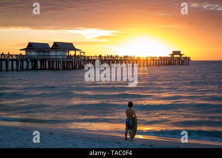 Los jóvenes surfer y colorido atardecer en el embarcadero, Naples, Florida, EE.UU. Imagen De Stock