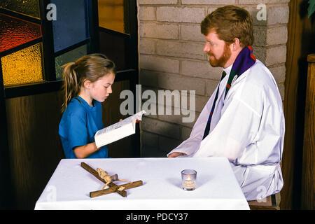 Chico leyendo la Biblia a sacerdote durante la reconciliación. © Myrleen Pearson ....Ferguson Cate Imagen De Stock