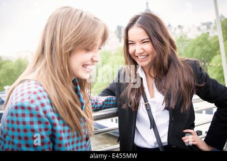 Dos jóvenes mujeres turistas cuchicheando en el Jubileo de Oro de la pasarela, London, UK Imagen De Stock