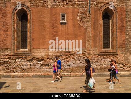 Los turistas que pasan delante de una iglesia, la región del Veneto, Venecia, Italia Imagen De Stock