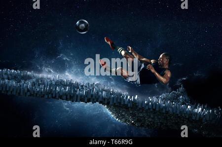 Jugador de fútbol masculino pateando una pelota de fútbol contra fondo futurista Imagen De Stock