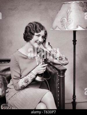 1920s sonriendo bien vestidos mujer hablando por teléfono candelabro - t2306 HAR001 HARS longitud media estimadas personas B&W Candelabro bonita morena felicidad alegre estilos de peinado TULIPA DE SONRISAS TELÉFONOS DEDO ONDAS FLOOR LAMP CONEXIÓN teléfonos Alegre elegante moda mujer adulta joven EN BLANCO Y NEGRO la etnia CAUCÁSICA HAR001 ANTICUADO Imagen De Stock