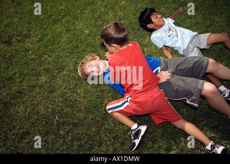 Los muchachos desbastado vivienda fuera del césped Imagen De Stock