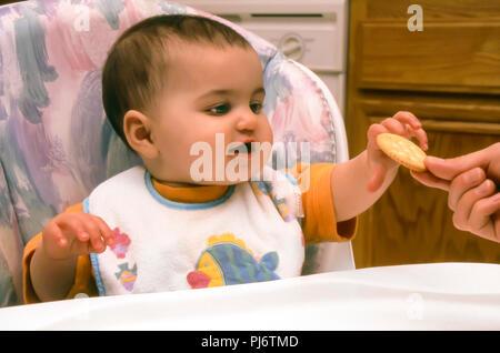 Niña sentada en una trona silla alta alcanzando cracker de madre de la mano. El Sr. © Myrleen Pearson ...Cate Ferguson Imagen De Stock