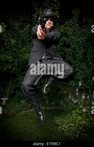 Un hombre en un traje de estilo antiguo, un sombrero y gafas de sol salta mientras apunta con una pistola. Imagen De Stock