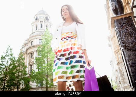 Mujer joven de pie en la calle de Londres, llevando bolsas de la compra. Imagen De Stock