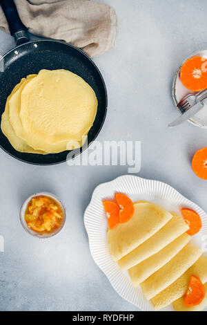 Sin Gluten panqueques en una sartén antiadherente y en una placa oval blanco adornado con rodajas de naranja, acompañado de mermelada de naranja. Imagen De Stock