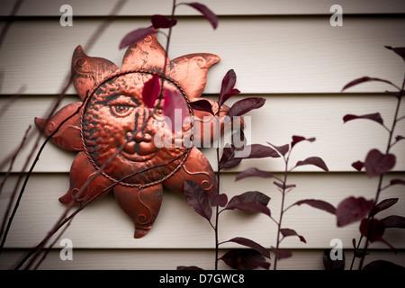 Un sonriente sol rostro ornamento metálico colgado en una pared. Imagen De Stock