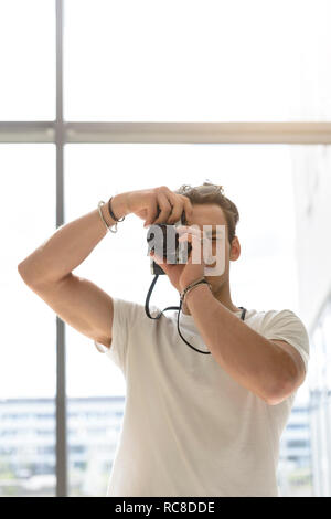 El hombre toma de fotografía, pared de vidrio en el fondo Imagen De Stock