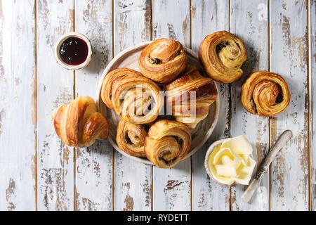 Variedad de bollos de hojaldre casera rollos de canela y croissant con mermelada, mantequilla como desayuno sobre fondo blanco tablón de madera. Sentar planas, s Imagen De Stock