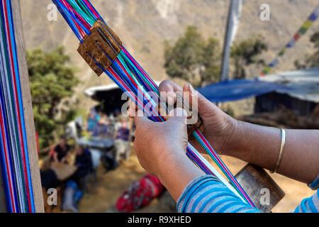Primer plano de una mujer tejedora de Nepal creando un colorido cinturón, Imagen De Stock