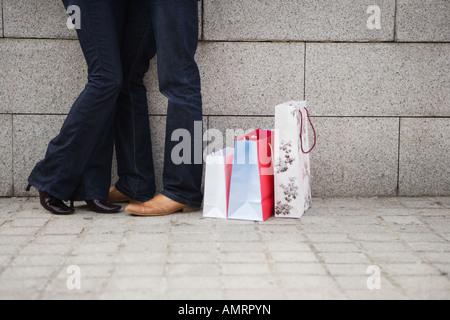 Par abrazar en la calle urbana, con bolsas de la compra. Imagen De Stock