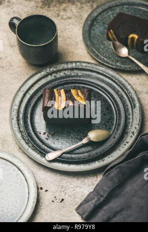 Trozos de chocolate recién horneadas torta de pan de banana postre de placa de cerámica gris sobre hormigón de fondo de la tabla, vista superior, el enfoque selectivo Imagen De Stock