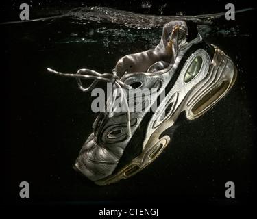 Un viejo y desgastado zapatilla de tenis flotadores sumergidos en el agua. Imagen De Stock