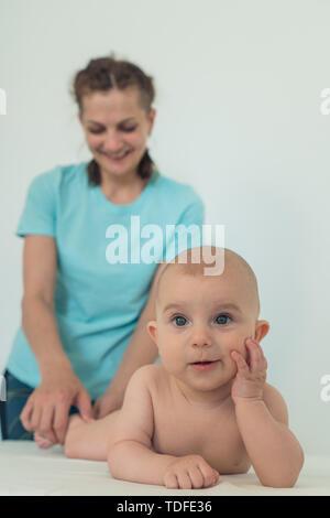 Mujer con risa funny lindo bebé. Gracioso kid posando para la cámara Imagen De Stock