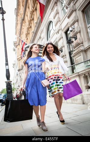 Dos mujeres jóvenes caminando por London Street llevar bolsas de la compra. Imagen De Stock