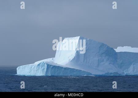 Parte de un iceberg reflejando la luz en un día nublado en el Antarctic Sound en la Península Antártica, en la Antártida Imagen De Stock