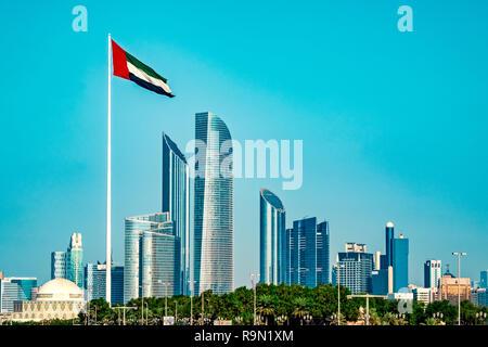 La foto muestra el contorno de la ciudad de Abu Dhabi, tomada desde el mar. Una bandera de la AEU está saludando en primer plano. Imagen De Stock
