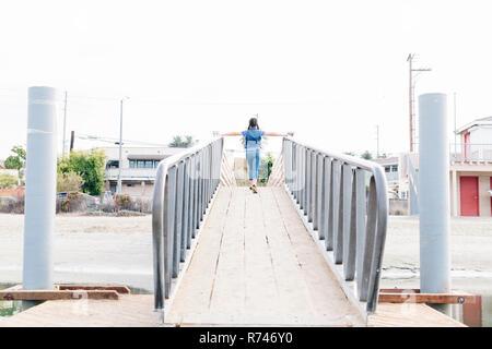 Chica cruzar el puente, Long Beach, California, EE.UU. Imagen De Stock