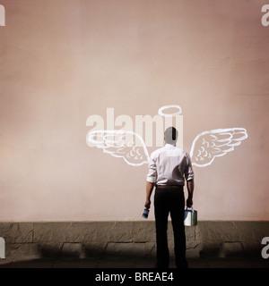 Hombre con alas de ángel pintado en una pared. Imagen De Stock