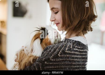 Chica sujetando lindo, cobaya pelo largo Imagen De Stock