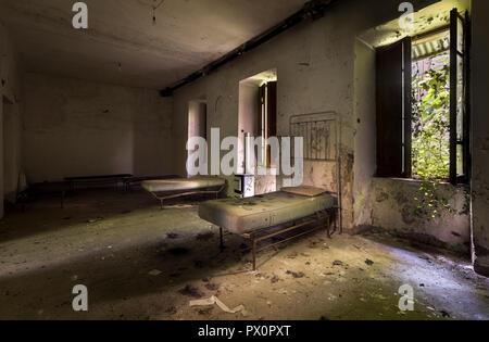 Vista desde el interior de una habitación con dos camas en un edificio abandonado. Imagen De Stock