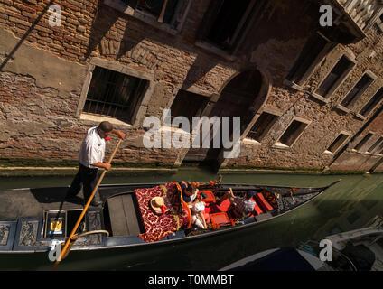 La góndola en un canal con los turistas, la región del Veneto, Venecia, Italia Imagen De Stock