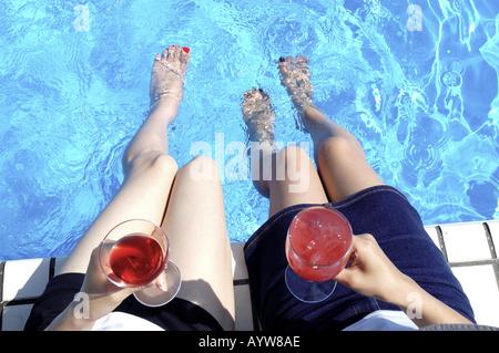 Dos mujeres sentadas al lado de la piscina con bebidas frías Imagen De Stock