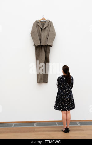 Mujer mirando su instalación de arte, sentía palo ( Filzanzug) por Joseph Beuys en la Hamburger Bahnhof museo de arte en Berlín, Alemania Imagen De Stock