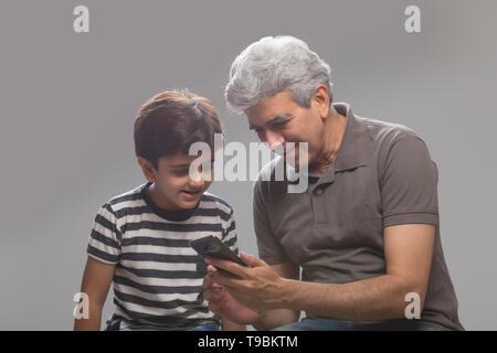 Abuelo y nieto a través de teléfono móvil Imagen De Stock